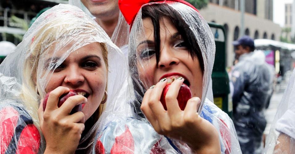 2.jun.2013 - Debaixo de chuva, participantes posam com maçã durante Parada Gay de São Paulo, na avenida Paulista