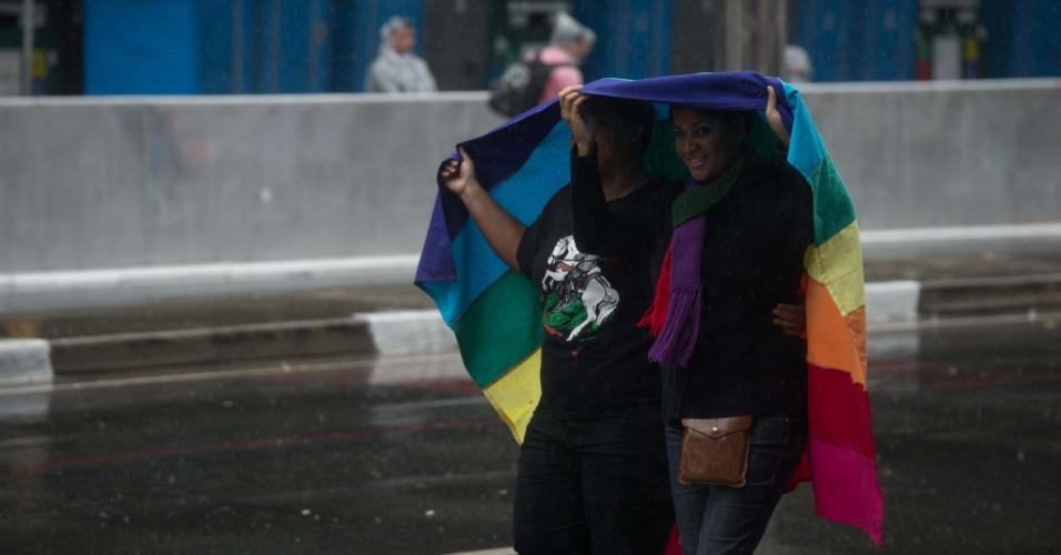 2.jun.2013 - Manifestantes usam bandeira nas cores do arco-íris, símbolo do movimento LGBT (Lésbicas, Gays, Bissexuais, Travestis, Transexuais e Transgêneros), para se proteger da chuva durante a 17ª edição da Parada Gay de São Paulo, realizada na avenida Paulista, região central da capital