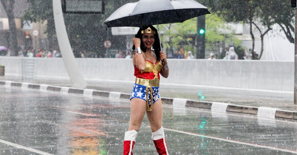 2.jun.2013 - Participante fantasiado de Mulher Maravilha caminha pela avenida Paulista debaixo de chuva durante concentração para a Parada Gay de São Paulo