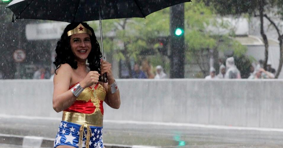 2.jun.2013 - Participante fantasiado de Mulher Maravilha aguarda debaixo de chuva o início da Parada Gay de São Paulo, na avenida Paulista, na manhã deste domingo