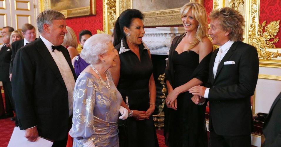 3.jun.2013 - Rainha Elizabeth 2ª (segunda à esq.) conversa com o cantor inglês Rod Stewart (à dir) e sua mulher, Penny Lancaster (segunda à dir.), durante recepção no Instituto Real para os Cegos, no palácio de Saint James, em Londres. No último domingo (2), a rainha completou 60 anos de reinado