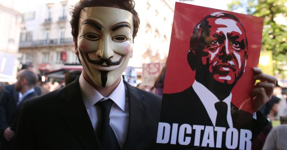 """4.jun.2013 - Homem usa máscara e segura cartaz com o rosto do primeiro-ministro turco, Recep Tayyip Erdogan, acima da palavra """"ditador"""", em Paris (França), durante protesto de apoio às manifestações anti-governo que vem ocorrendo na Turquia"""