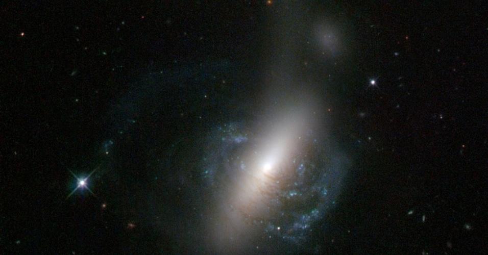 4.jun.2013 - O telescópio espacial Hubble captou o choque de duas galáxias que causou a expulsão de muitas estrelas ao espaço (topo da imagem). Segundo a Nasa (Agência Espacial Norte-Americana), a galáxia espiral ESO 576-69 (identificada pelo brilho no centro da imagem) foi ejetada do sistema com a colisão, o que ajudou a produzir a 'faixa' de estrelas