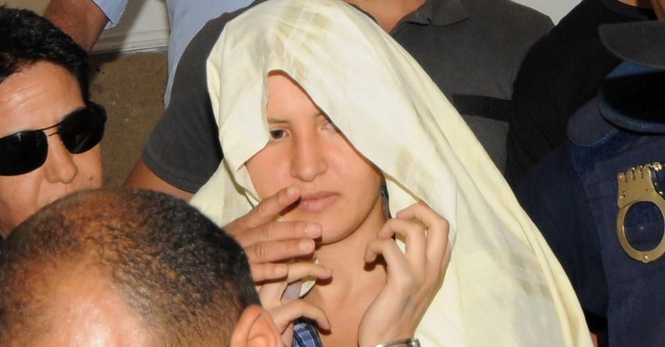 5.jun.2013 - Amina Sboui, tunisiana membro do grupo feminista ucraniano Femen, chega algemada e com a cabeça coberta em tribunal da cidade tunisiana de Kairouan, nesta quarta-feira (5). Ela será julgada por postar no Facebook fotos de si mesma mostrando os seios e por pichar a palavra