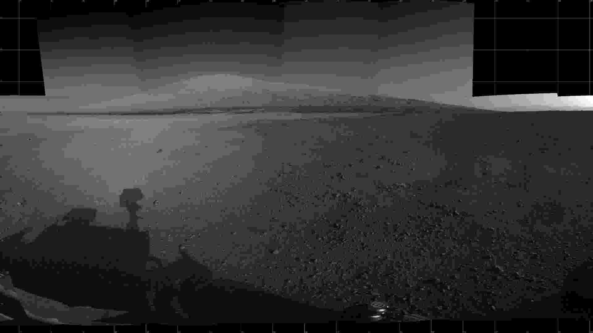 6.jun.2013 - Cientistas da Nasa (Agência Espacial Norte-Americana) enviaram na segunda-feira (5) comandos para o Curiosity se movimentar e começar a dirigir rumo à base do monte Sharp (ao fundo), localizado cerca de oito quilômetros a sudoeste de sua posição atual. Como a viagem deve durar meses, o robô fará três paradas para estudos científicos, como determinar o quanto mais seca fica essa região do planeta vermelho à medida que ele se afasta da baía Yellowknife. Acima, imagem do monte Sharp, que tem 5,5 quilômetros de altura, feita pelo robô em agosto do ano passado, mês que iniciou sua missão de dois anos - Nasa/JPL-Caltech