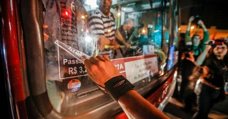 """7.jun.2013 - Manifestantes retiram adesivo de ônibus enquanto protestam contra o aumento da tarifa do transporte público em São Paulo (SP), na região do largo da Batata, na zona oeste. O valor da tarifa subiu de R$ 3 para R$ 3,20. Manifestantes carregam cartazes, bandeiras e já entregam folhetos com informações sobre o próximo protesto, marcado para as 17h de terça-feira (11) na praça do Ciclista, na avenida Paulista. O tema do protesto é """"Se a tarifa não baixar, São Paulo vai parar"""""""