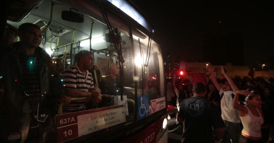 """7.jun.2013 - Ônibus passa por meio de manifestantes que protestam contra o aumento da tarifa de ônibus no largo da Batata, região oeste de São Paulo, no segundo dia de protestos na capital. O valor subiu de R$ 3 para R$ 3,20. Manifestantes carregam cartazes, bandeiras e já entregam folhetos com informações sobre o próximo protesto, marcado para as 17h de terça-feira (11) na praça do Ciclista, na avenida Paulista. O tema do protesto é """"Se a tarifa não baixar, São Paulo vai parar"""""""