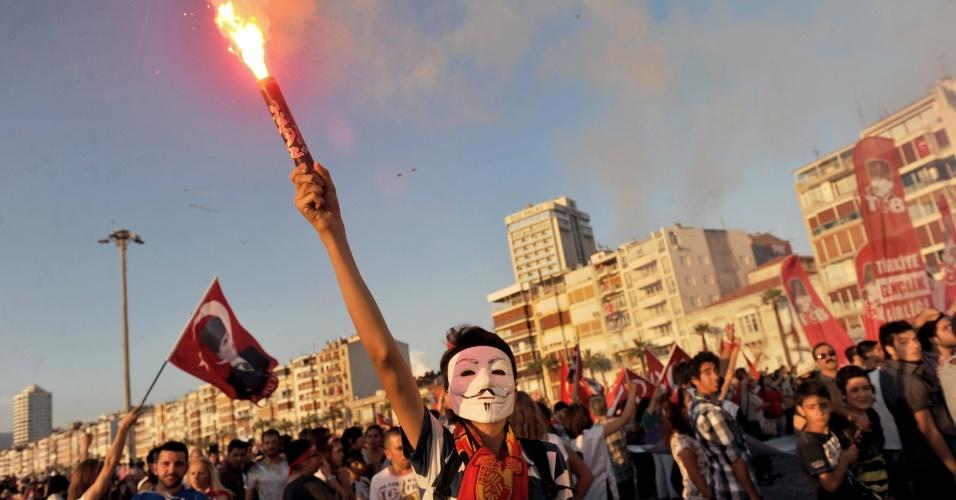 9.jun.2013 - Manifestante turco usa sinalizador e máscara na praça Gundogdu, em Ismir, Turquia, em mais uma noite de protestos pelo país. Dezenas de milhares de manifestantes voltaram a lotar as ruas de várias cidades turcas na noite deste sábado (8), desafiando o primeiro-ministro turco, Recep Tayyip Erdogan, que pediu para acabarem com a revolta civil. A onda de protestos começou com uma manifestação contra derrubadas de árvores de um parque em Istambul em 31 de maio, que terminou em um violento conflito entre manifestantes e a polícia. A repressão aumentou a insatisfação com o governo turco, visto cada vez mais como autoritário