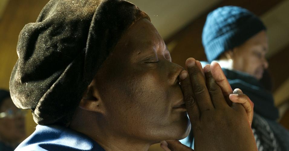 9.jun.2013 - Mulher faz oração em igreja no bairro de Soweto, em Johannesburgo, em missa pelo ex-presidente Nelson Mandela, 94, que está hospitalizado em estado grave em Pretória, na África do Sul. O bairro foi um importante polo de resistência ao regime de segregação racial do apartheid, adotado no país entre 1948 a 1994