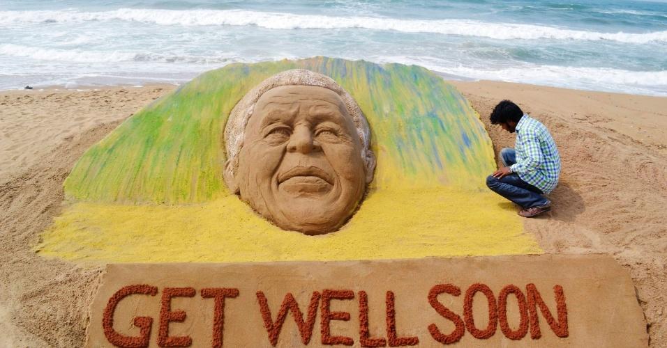 """O artista indiano Sudarshan Pattnaik cria escultura de areia desejando uma rápida recuperação ao ex-presidente sul-africano Nelson Mandela, em Puri, no Estado indiano de Odisha, neste domingo (9). Na areia, lê-se (em tradução livre): """"Fique bem logo"""". Mandela, 94, está internado em estado grave, devido a uma pneumonia"""