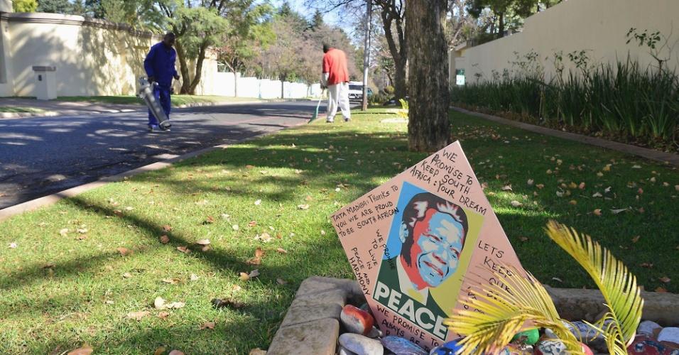 """10.jun.2013 - Jardineiros limpam área do lado de fora da casa do ex-presidente sul-africano Nelson Mandela, Johannesburgo, em onde foi colocado um cartão em homenagem ao ex-líder. O herói da luta contra o apartheid permanece no hospital pelo terceiro dia seguido com uma infecção pulmonar, e seu estado de saúde continua """"grave, mas estável"""", inalterado desde sábado (8), informou o governo"""