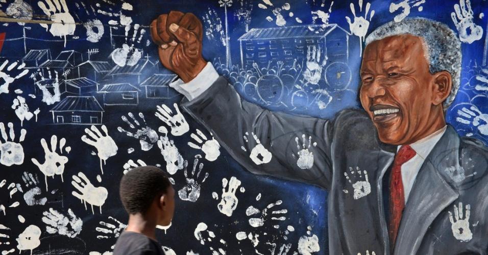 """9.jun.2013 - Garoto anda por muro pintado em homenagem a Nelson Mandela, do lado de fora da casa do ex-presidente sul-africano, em Johannesburg. O herói da luta contra o apartheid permanece no hospital pelo terceiro dia seguido com uma infecção pulmonar, e seu estado de saúde continua """"grave, mas estável"""", inalterado desde sábado (8), informou o governo"""