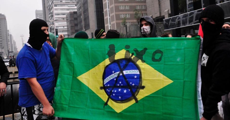 11.jul.2013 - Manifestantes anarquistas picham bandeira do Brasil durante protesto pela redução das tarifas do transporte público em São Paulo