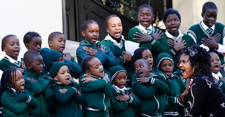 """11.jun.2013 - Crianças da Escola Cristã Rainbow-Hill cantam do lado de fora da casa do ex-presidente da África do Sul Nelson Mandela, para desejar que ele fique melhor, nesta terça-feira (11). Mandela permanece no hospital pelo quarto dia e seu estado ainda é """"sério, mas estável"""", segundo governo"""