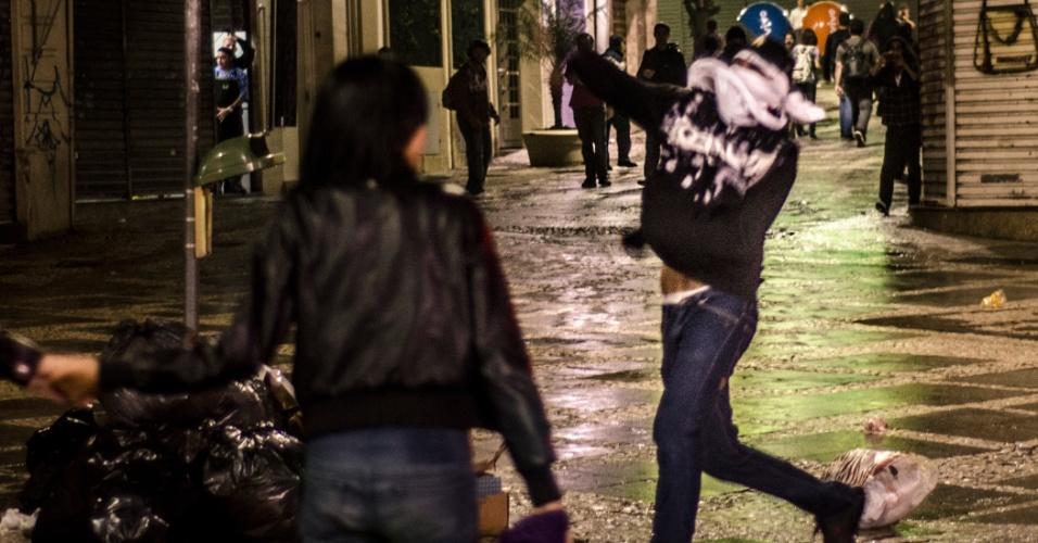 11.jun.2013 - Manifestante atira pedra contra policiais em uma das vias próximas à Catedral da Sé, no centro de São Paulo