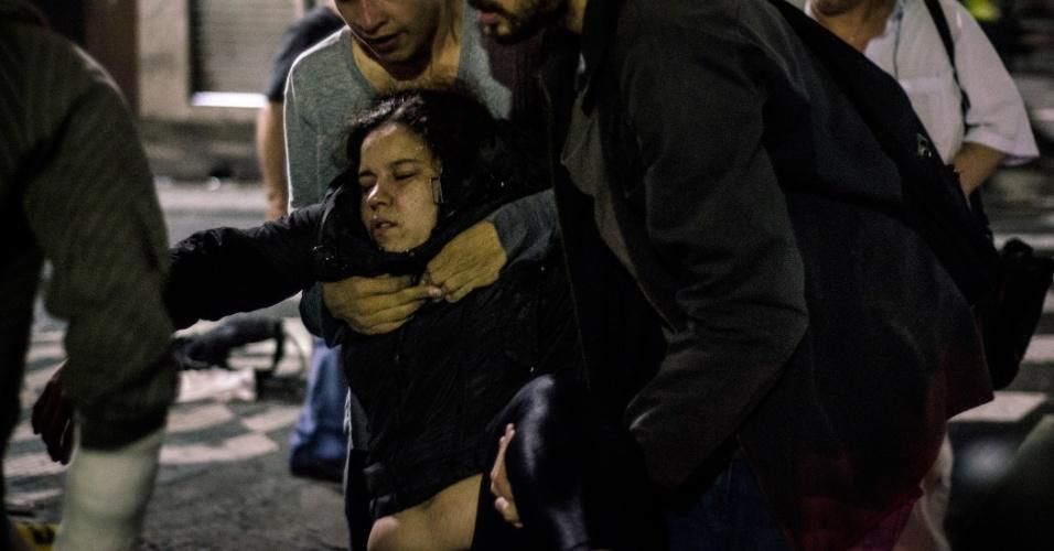11.jun.2013 - Manifestantes socorrem mulher que passava de moto por locais onde policiais dispararam grande quantidade de gás lacrimogênio. A mulher desmaiou após respirar o gás