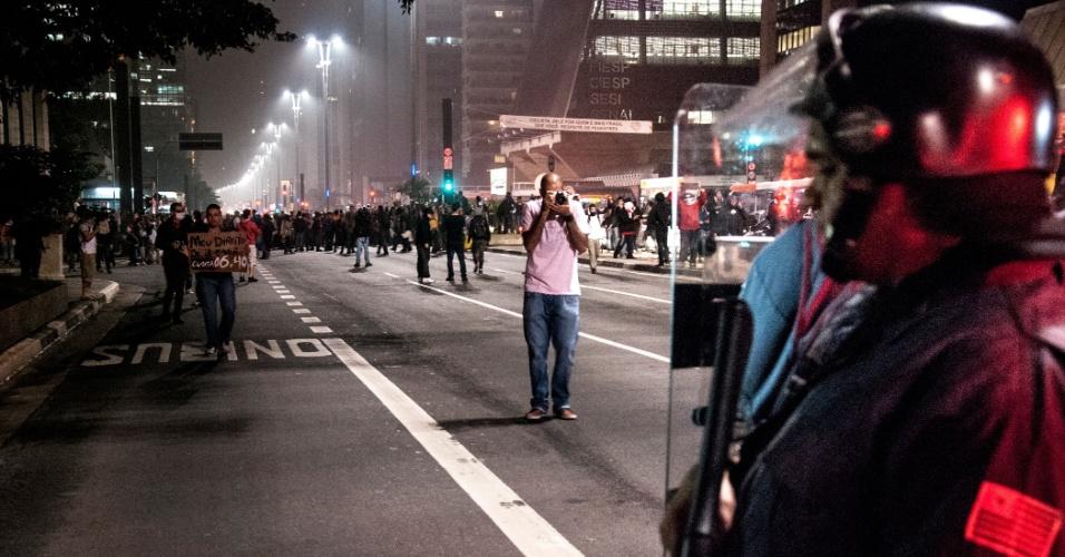 11.jun.2013 - Policial observa movimentação dos manifestantes na avenida Paulista, região central da capital paulista, momentos antes das agressões das forças de segurança reiniciarem