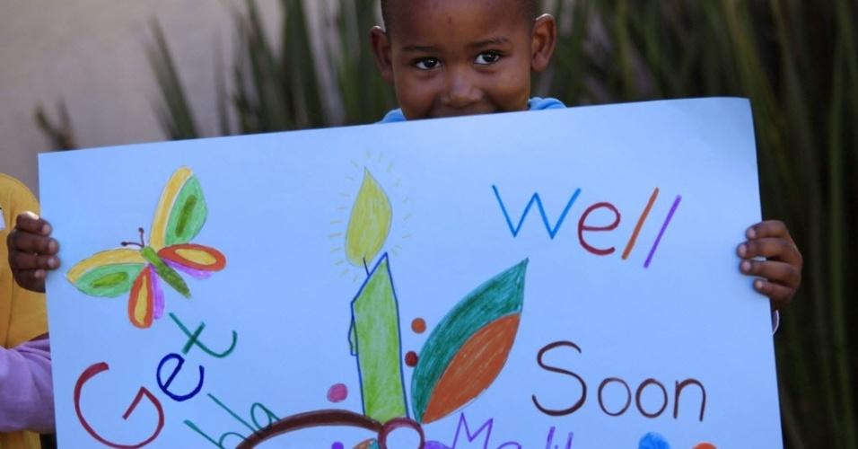 12.jun.2013 - Crianças seguram cartazes e cantam pela recuperação do ex-presidente da África do Sul, Nelson Mandela, no hospital há cinco dias, fora de sua residência em Joanesburgo. Mandela está respondendo melhor ao tratamento, informou nesta quarta-feira o presidente da África do Sul, Jacob Zuma