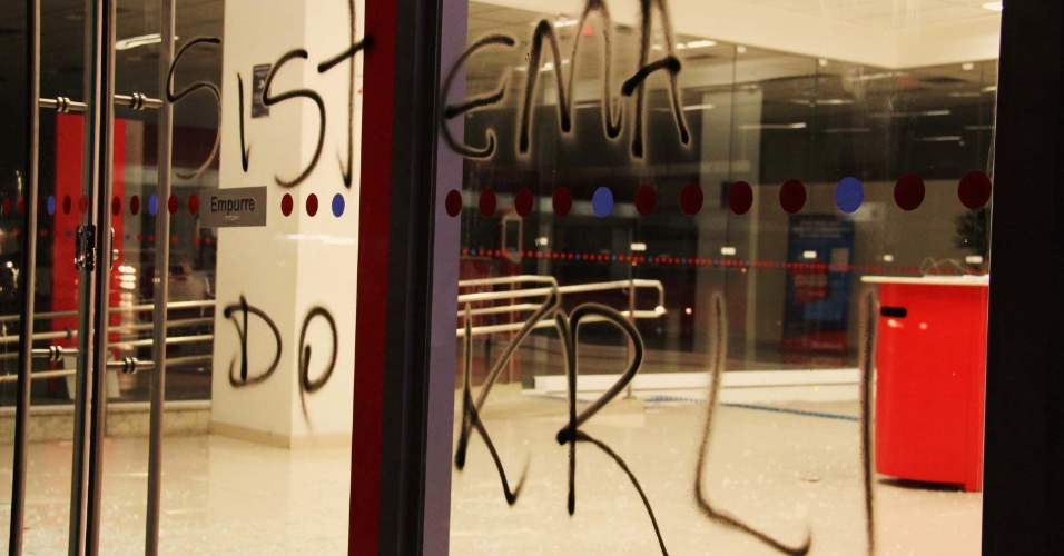 12.jun.2013 - Vidro de agência bancária na região central de São Paulo é pichado durante o terceiro protesto pela redução da tarifa de ônibus, na noite desta terça-feira (11)