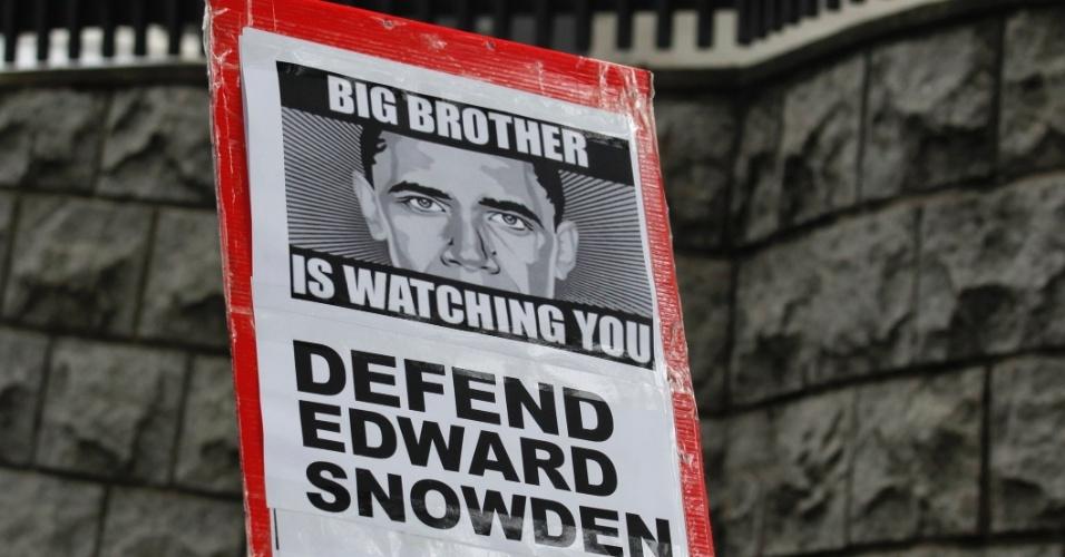 """13.jun.2013 - Manifestante apoiador de Edward Snowden, ex-consultor da Agência Nacional de Inteligência (NSA, na sigla em inglês) dos Estados Unidos que assumiu a responsabilidade pelos recentes vazamentos sobre a espionagem americana, carrega cartaz em que o rosto do presidente Barack Obama aparece entre a frase """"O Grande Irmão está vigiando você"""", em referência ao livro """"1984"""", de George Orwell, em frente ao consulado dos Estados Unidos em Hong Kong, na China, país onde Snowden busca asilo"""