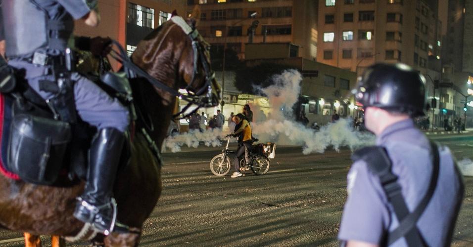 13.jun.2013 - Mulher anda de bicicleta em meio a confronto entre policiais e manifestantes durante quarto ato contra o aumento da tarifa do transporte coletivo realizado pelas ruas da região central de São Paulo
