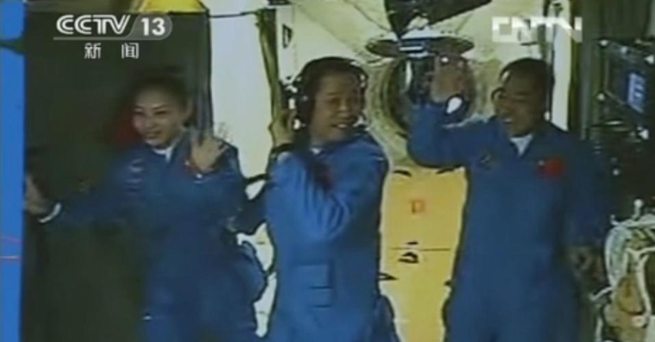 13.jun.2013 - Os astronautas chineses Wang Yaping, Nie Haisheng e Zhang Xiaoguang (da esquerda para a direita) acenam para as câmeras ao entrarem no módulo espacial Tiangong 1, nesta quinta-feira (13). A manobra de acoplamento automática da nave espacial ocorreu com sucesso às 13h18 locais (às 2h18, no fuso de Brasília)
