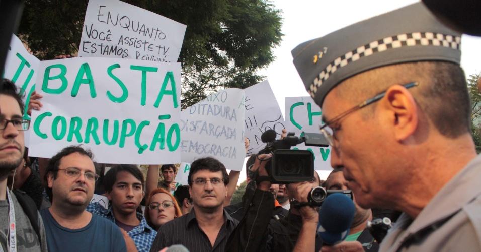 14.jun.2013 - Manifestantes e jornalistas questionam policial posicionado em frente a sede da Rede Globo em um novo protesto na região da avenida Berrini, zona sul de São Paulo, nesta sexta-feira, contra o aumento da passagem de ônibus, trens e metrô em São Paulo (SP).O valor da passagem passou de R$ 3 para R$ 3,20. A noite desta quinta-feira (13), o quarto dia de protestos na cidade, foi considerado o mais violento. Mais de 200 pessoas foram detidas e houve vários registros de agressão policial frente aos manifestantes, jornalistas e transeuntes