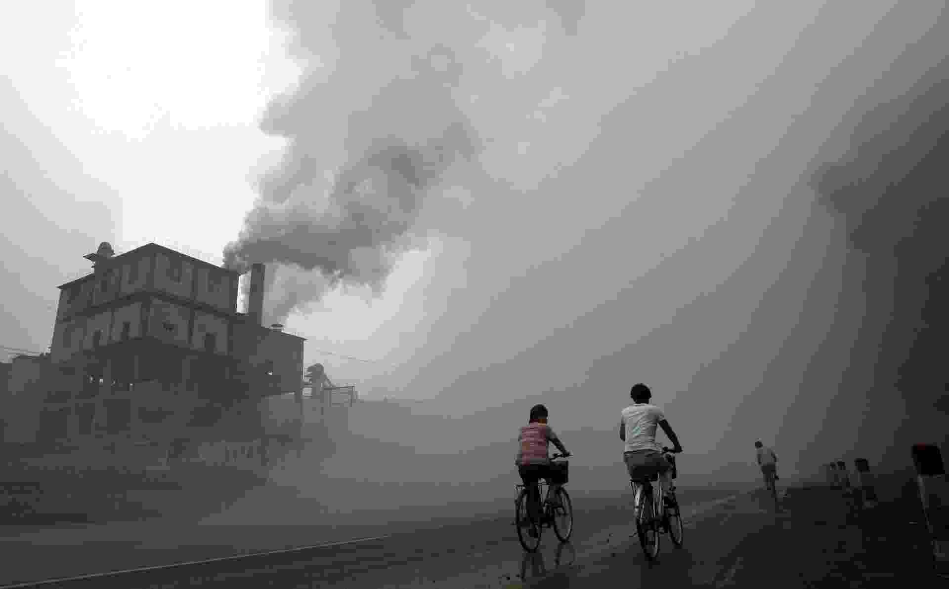 14.jun.2013 - O aquecimento global é provocado pela emissão de gases como CO2 e metano. A China é a maior poluidora do mundo, principalmente pela queima de combustíveis fósseis. Ciclistas passam por ruas cobertas por fumaça emitida por indústria em Yutian, a cem quilômetros de Pequim - Peter Parks/AFP