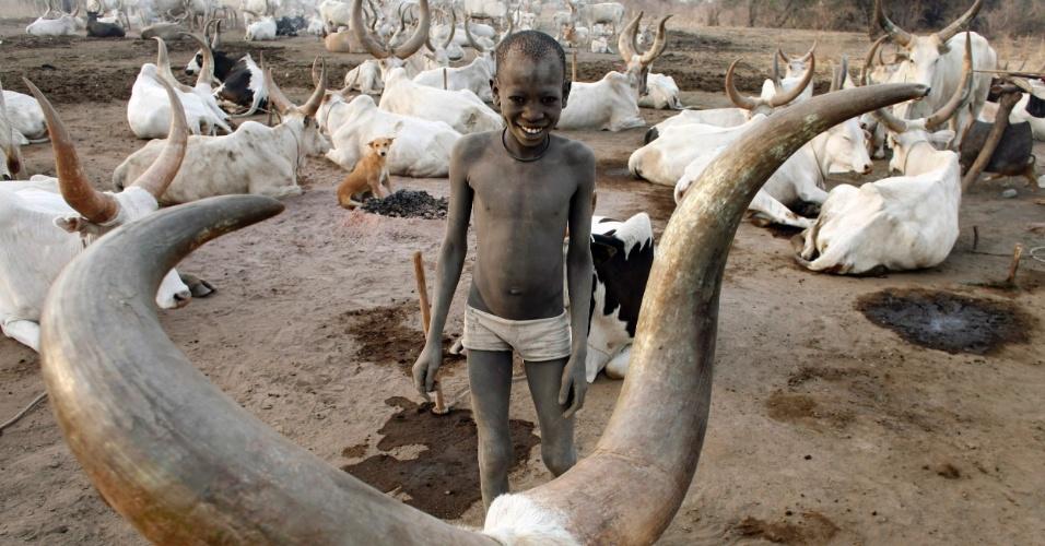 17.jun.2013 - 2011 - Criança da tribo Mundari brinca em meio ao gado próximo a Terekeka, no sul do  Sudão. O país sofreu com a falta de pastos