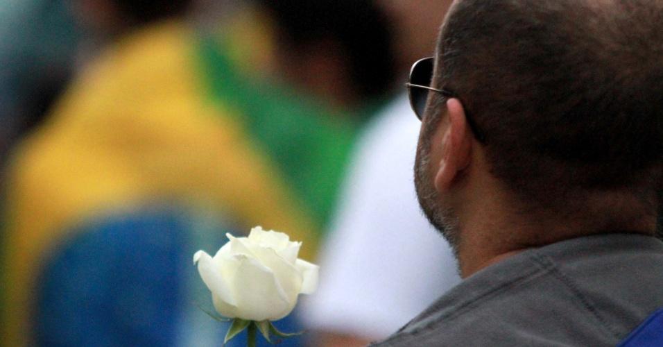 17.jun.2013 - Homem segura rosa branca durante protesto no centro do Rio de Janeiro, nesta segunda-feira (17), contra o reajuste da tarifa de ônibus na cidade e os gastos com a Copa do Mundo. A manifestação teve início às 17h, com saída da Candelária rumo à avenida Rio Branco