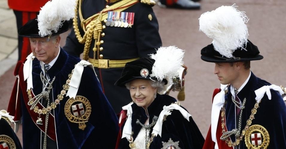 17.jun.2013 - Rainha Elizabeth 2ª, do Reino Unido (centro), caminha com o príncipe Charles, príncipe de Gales (à esq.), e o príncipe William, duque de Cambridge (à dir.), durante a parada anual da Ordem da Liga, importante ordem de cavalaria da Inglaterra, no castelo de Windsor, em Berkshire, leste de Londres, nesta segunda-feira (17)