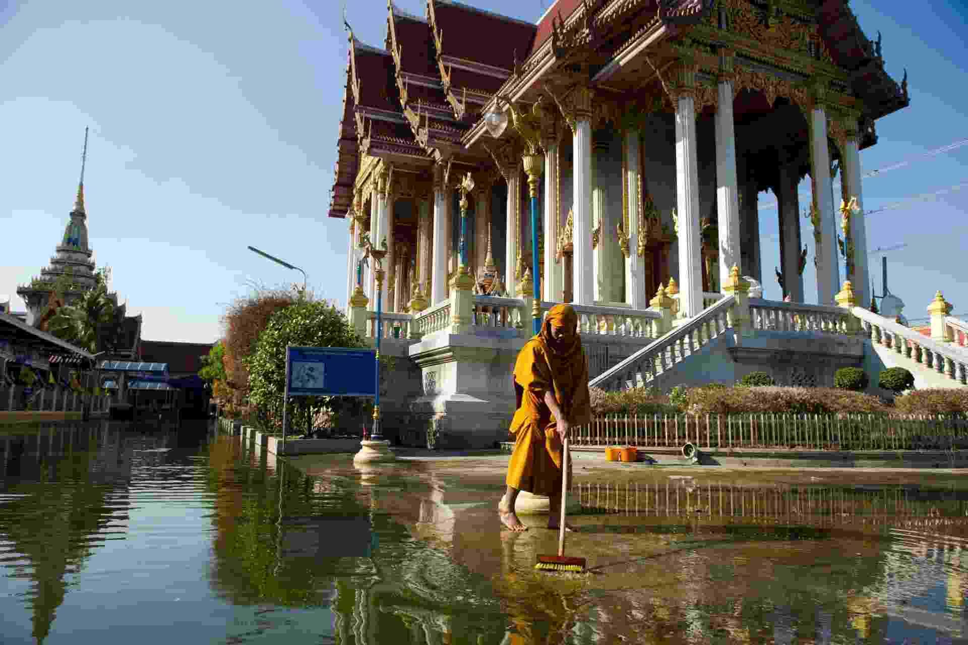 17.jun.2013 -2011: Monge budista limpa entrada de templo em Don Muang, distrito de Bangcoc, na Tailândia. Mais de 5,4 milhões de pessoas foram afetadas pela enchente, uma das piores nos últimos 50 anos do país - Nicolas Aafouri/AFP
