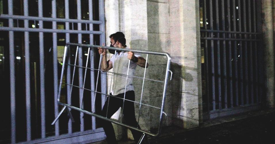18.jun.2013 - Manifestante tenta invadir a sede da Prefeitura de São Paulo, na região central da cidade, jogando cerca de proteção na entrada, na noite desta terça-feira. A Guarda Civil Metropolitana responde com bombas de gás lacrimogêneo. Milhares de manifestantes saíram da Praça da Sé até a prefeitura no sexto dia de protestos. A manifestação que começou contra o aumento das passagens de ônibus, trem e metrô na cidade, organizado pelo Movimento Passe Livre, abraçou outras causas. Outro protesto realizado na noite desta segunda-feira (17) reuniu mais de 60 mil pessoas na capital paulista e foi pacífico por quase todo o trajeto. No fim da noite, um grupo tentou invadir o Palácio do Governo, na zona sul, e foi reprimido pela polícia