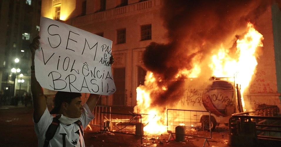18.jun.2013 - Veículo da TV Record estacionado em frente à Prefeitura de São Paulo é incendiado nesta terça-feira (18), sexto dia dos protestos que começaram contra o aumento da tarifa do transporte coletivo. Um grupo tentou invadir o local, e houve confronto com a Guarda Civil Metropolitana