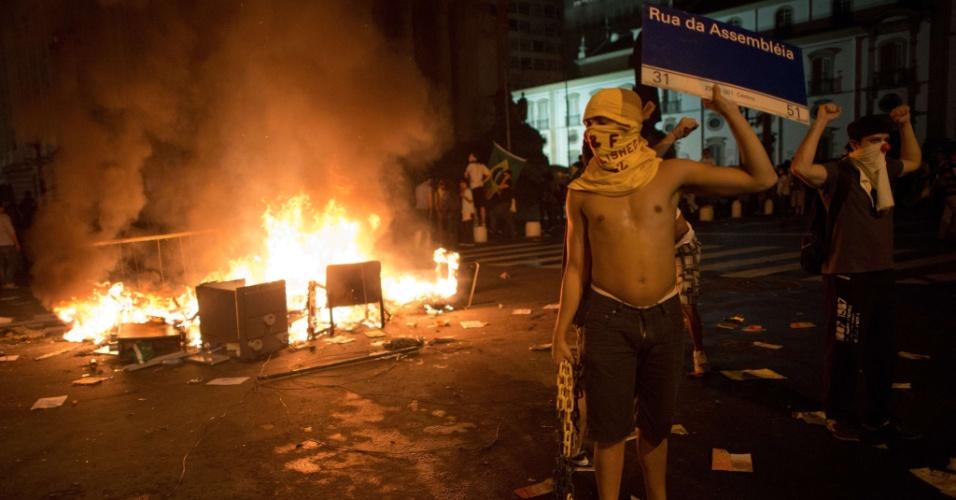 Manifestante segura placa da rua da Assembleia, durante os protestos nos arredores da Assembleia Legislativa do Rio de Janeiro