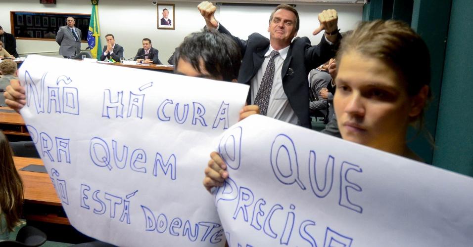 """Manifestantes protestam na Comissão de Direitos Humanos da Câmara contra a aprovação do projeto de lei que determina o fim da proibição, pelo Conselho Federal de Psicologia, de tratamentos que se propõem a reverter a homossexualidade (""""cura gay"""") na tarde desta terça-feira (18), em Brasília. A sessão que aprovou a proposta foi presidida hoje pelo deputado pastor Marco Feliciano (PSC-SP). Na foto, o deputado Jair Bolsonaro, atrás dos manifestantes, reprova o protesto"""