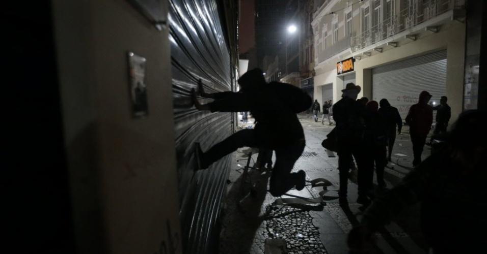 18.jun.2013 - Manifestante arromba porta de loja durante o sexto protesto contra o aumento das tarifas do transporte público no centro de São Paulo, na noite de terça-feira (19). Com o arrombamento das portas, as lojas foram alvos de saques de eletrônicos, eletrodomésticos e brinquedos