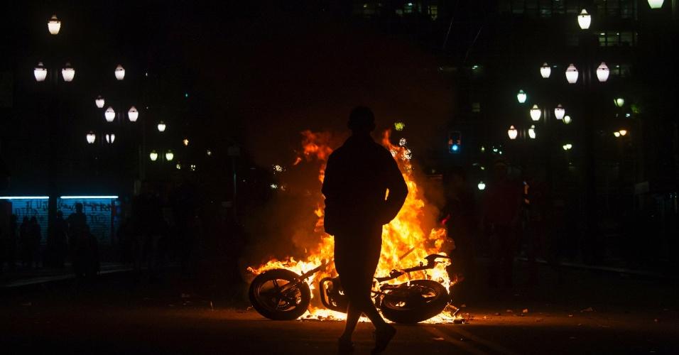 18.jun.2013 - Manifestante fica em frente à motocicleta incendiada no centro de São Paulo durante o sexto protesto contra o aumento das tarifas do transporte público na cidade, realizado na noite desta terça-feira (18). Um grupo de manifestantes destruiu agências bancárias e depredou uma série de estabelecimentos na praça do Patriarca e na rua Direita. Com o arrombamento das portas, as lojas foram alvos de saques de eletrônicos, eletrodomésticos e brinquedos
