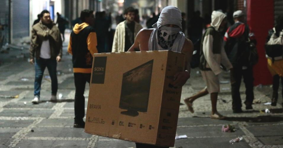 18.jun.2013 - Manifestante leva TV de LED após uma série de estabelecimentos serem saqueados no centro de São Paulo durante o sexto protesto contra o aumento das tarifas do transporte público na cidade. Com o arrombamento das portas, as lojas foram alvos de saques de eletrônicos, eletrodomésticos e brinquedos