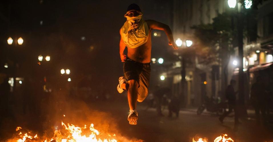 18.jun.2013 - Manifestante pula barricada de lixo incendiado no centro de São Paulo durante o sexto protesto contra o aumento das tarifas do transporte público na cidade, realizado na noite desta terça-feira (18). Um grupo de manifestantes destruiu agências bancárias e depredou uma série de estabelecimentos na praça do Patriarca e na rua Direita. Com o arrombamento das portas, as lojas foram alvos de saques de eletrônicos, eletrodomésticos e brinquedos