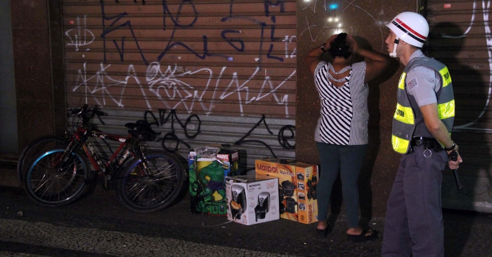18.jun.2013 - Mulher é presa na praça do Patriarca com vários produtos eletro-eletrônicos saqueados em lojas durante protesto do Movimento Passe Livre contra o aumento da tarifa de ônibus, no centro de São Paulo, na noite desta terça-feira (18). Ela foi encaminhada para o 8° DP