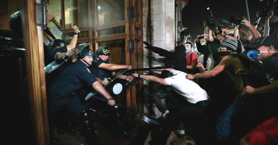 18.jun.2013 - Policiais contem manifestantes que tentam invadir a Prefeitura de São Paulo durante o sexto protesto contra o aumento das tarifas do transporte público na cidade, realizado na noite desta terça-feira (18). Um grupo de manifestantes destruiu agências bancárias e depredou uma série de estabelecimentos na praça do Patriarca e na rua Direita. Com o arrombamento das portas, as lojas foram alvos de saques de eletrônicos, eletrodomésticos e brinquedos