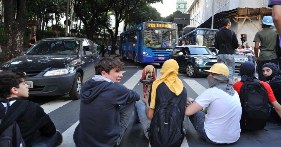 19.jun.2013 - Estudantes se sentam em avenida de Belo Horizonte (MG), impedindo os carros de passarem, durante protesto que reúne 5.000 pessoas na tarde desta quarta-feira. Pelo terceiro dia seguido, integrantes de movimentos sociais e estudantes saem às ruas para protestar contra o aumento das passagens, a corrupção e o serviço público oferecido à população