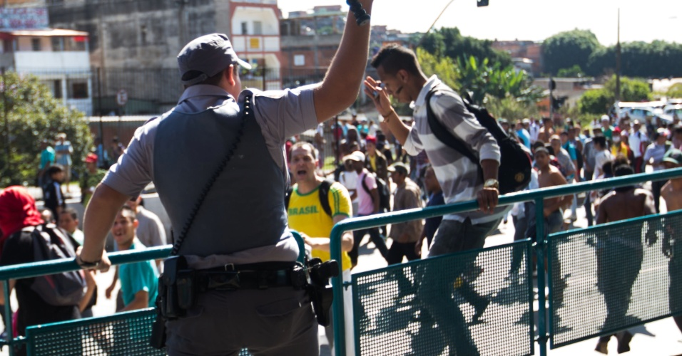 19.jun.2013 - Policial militar contem manifestantes que tentaram invadir o Terminal Jardim Ângela durante protesto na avenida M'Boi Mirim pela redução da tarifa do transporte público