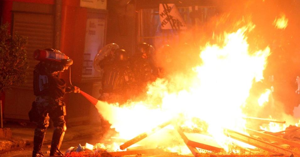 19.jun.2013 - Policial usa extintor para apagar o fogo próximo a um ônibus queimado por manifestantes durante protesto pela redução da tarifa de ônibus em Niterói. O ato de vandalismo ocorre horas depois de anunciada a revogação do aumento pela prefeitura