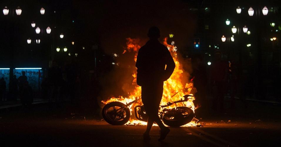 19.jun.2013 - Um manifestante observa na madrugada uma motocicleta incendiada durante os protestos em São Paulo