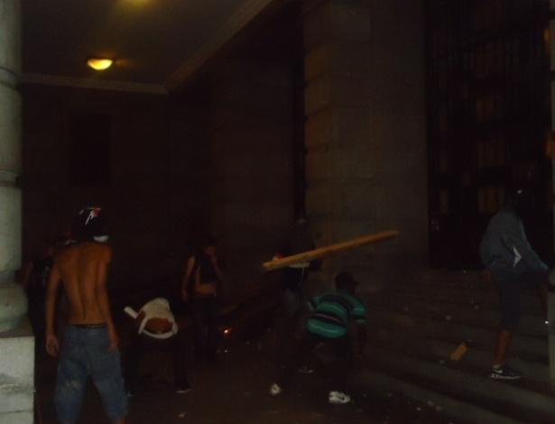 19.jun.2013 - Vândalos arremessam pedaços de madeira na porta da Prefeitura de Belo Horizonte, na madrugada desta quarta-feira (19). O segundo dia seguido de protestos na cidade terminou com vandalismo e ação da tropa de choque da Polícia Militar, que chegou por volta das 0h30 ao centro para conter um grupo de manifestantes que quebrou vidraças de lojas e bancos