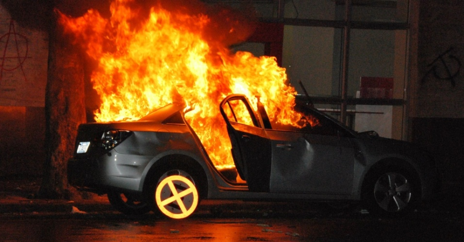 17.jun.2013 - Manifestantes colocam fogo em carro em frente ao prédio da Faculdade Cândido Mendes, no centro do Rio de Janeiro
