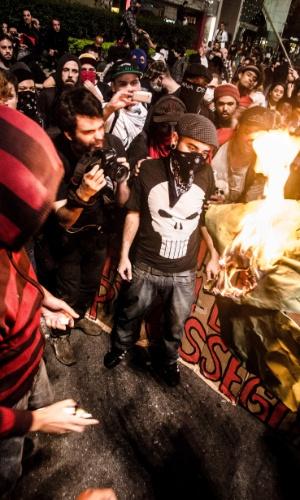"""20.jun.2013 - Manifestantes anarquistas ateiam fogo a bandeira brasileira aos gritos de """"essa bandeira mata índio"""", na avenida Paulista, na noite desta quinta-feira (20). Cerca de 110 mil pessoas compareceram a ato convocado pelo Movimento Passe Livre"""