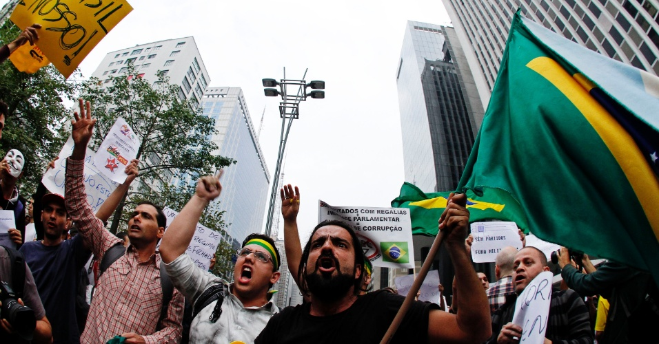 20.jun.2013 - Manifestantes erguem bandeiras e fecham os dois sentidos da avenida Paulista, na região central de São Paulo, no início da concentração para um protesto nesta quinta-feira (20), mantido mesmo após a redução das passagens de ônibus, metrô e trem na capital paulista, anunciada ontem